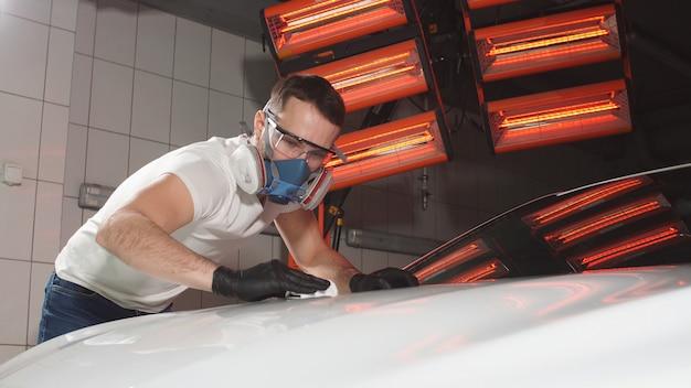 Młody człowiek w okularach i respiratorze poleruje samochód w warsztacie samochodowym
