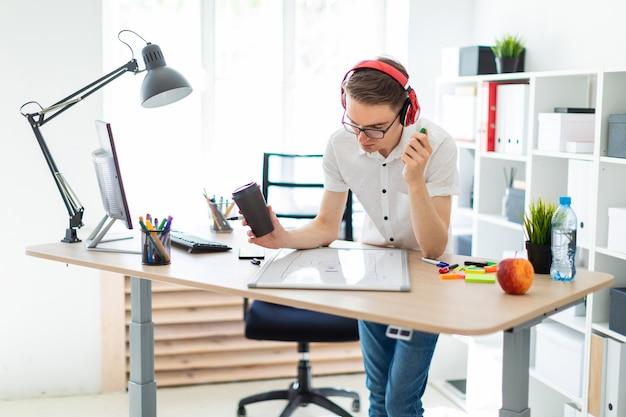 Młody człowiek w okularach i słuchawkach trzyma w rękach szklankę kawy i marker. przed tym facetem jest tablica magnetyczna.
