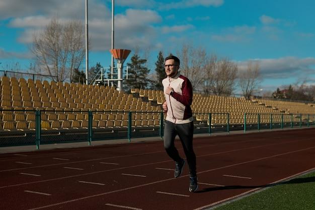 Młody człowiek w okularach jogging na stadionie