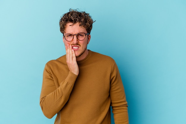 Młody człowiek w okularach na białym tle na niebieskiej ścianie o silnym bólu zębów, bólach trzonowych
