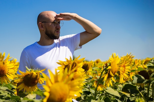 Młody człowiek w okularach patrzy w kierunku horyzontu na słonecznikowym polu w pogodny dzień.