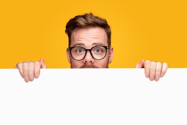 Młody człowiek w okularach pokazując pusty sztandar