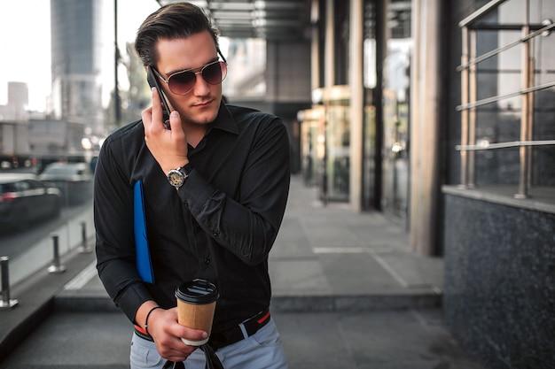 Młody człowiek w okularach przeciwsłonecznych chodzi oprócz budynku i rozmawia przez telefon. trzyma kubek i torbę w jednej ręce. facet jest zajęty.