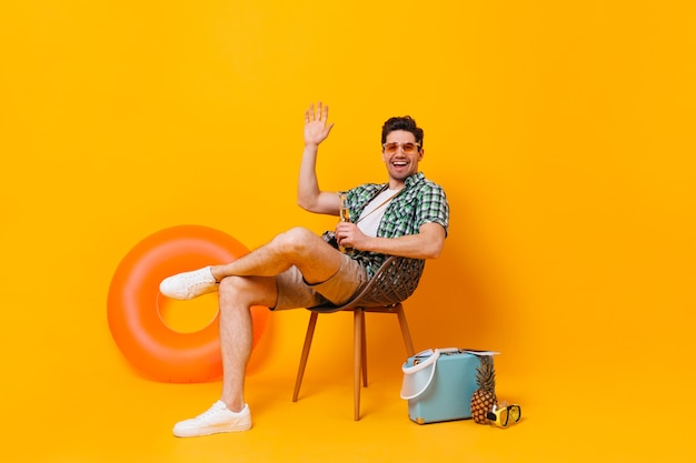 Młody człowiek w okularach przeciwsłonecznych cieszy się wakacjami na tle nadmuchiwanego koła i walizki. facet siedzi na drewnianym krześle, pije piwo i macha ręką.