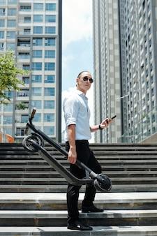 Młody człowiek w okularach przeciwsłonecznych, stojąc na schodach z hulajnogą i smartfonem w rękach i odwracając
