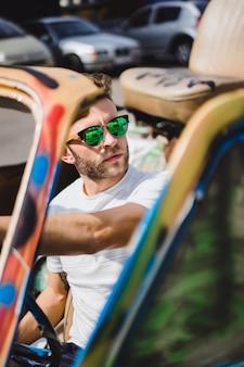 Młody człowiek w okularach przeciwsłonecznych w kabriolecie
