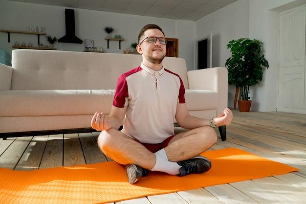 Młody człowiek w okularach robi joga na macie w domu