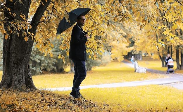 Młody człowiek w okularach spaceruje po parku z parasolem podczas deszczu.