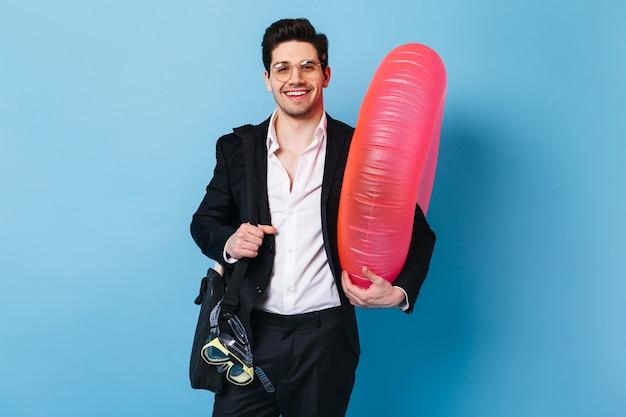 Młody człowiek w okularach uśmiecha się na niebieskiej przestrzeni. facet w czarnym garniturze i koszuli trzyma maskę do nurkowania i gumowy pierścień.