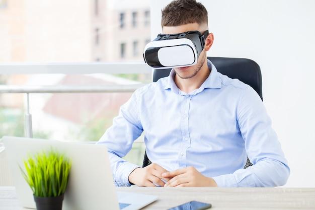 Młody człowiek w okularach wirtualnej rzeczywistości w nowoczesnym biurze.