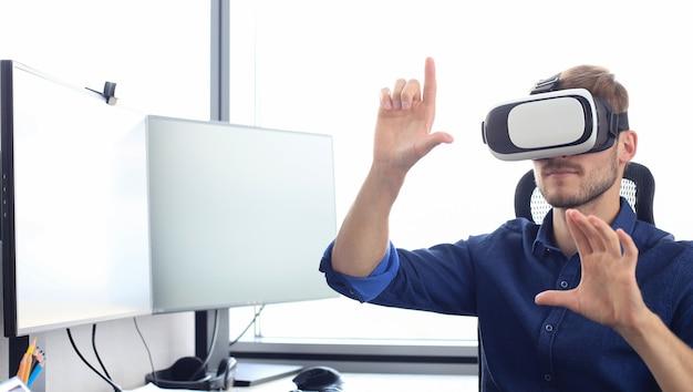 Młody człowiek w okularach wirtualnej rzeczywistości w nowoczesnym studiu coworkingowym.