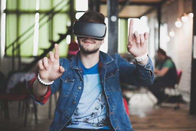 Młody człowiek w okularach wirtualnej rzeczywistości w nowoczesnym wnętrzu coworking studio. smartfon korzystający z gogli vr.
