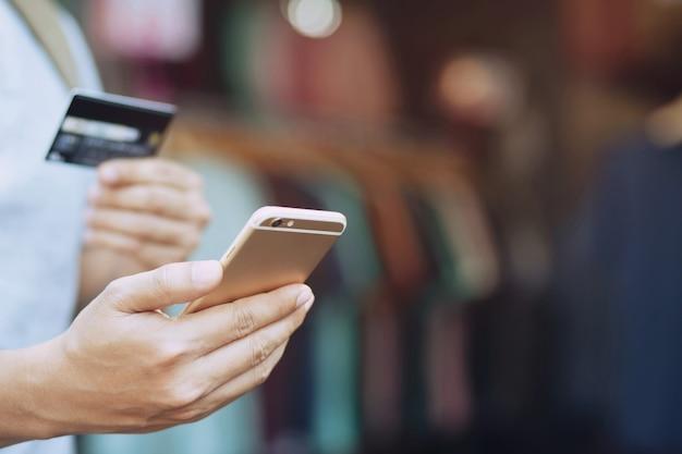 Młody człowiek w okularach zakupy online przy użyciu karty kredytowej za pomocą inteligentnego telefonu w domu.