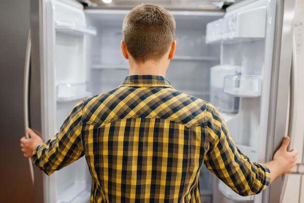 Młody człowiek w otwartej lodówce w sklepie elektronicznym. mężczyzna kupuje domowe urządzenia elektryczne na rynku