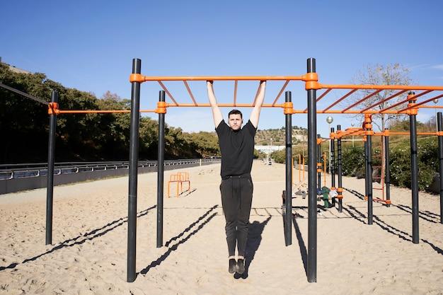 Młody człowiek w parku ze sztangą podciąga się, kalistenika. ćwiczenia ze sztangą na świeżym powietrzu, fitness, sport, trening i koncepcja stylu życia.