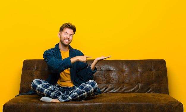 Młody człowiek w piżamach uśmiecha się, czuje się szczęśliwy, beztroski i zadowolony, wskazując na pojęcie lub pomysł na przestrzeni kopii na stronie. siedzieć na kanapie