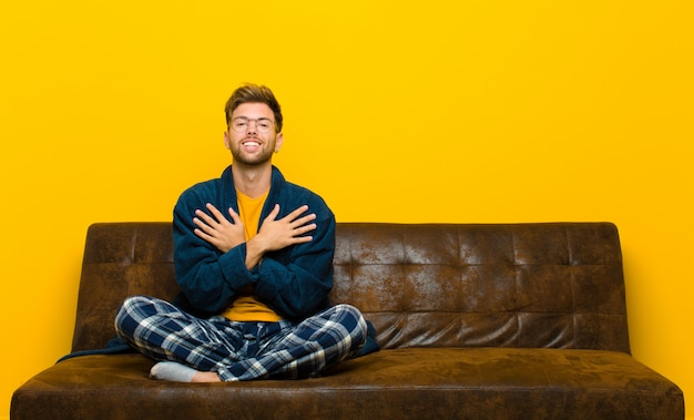 Młody człowiek w piżamie czuje się romantyczny szczęśliwy i zakochany, uśmiechając się wesoło i trzymając się za ręce blisko serca. siedzieć na kanapie