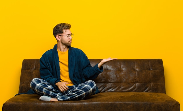 Młody człowiek w piżamie czuje się szczęśliwy i uśmiechnięty od niechcenia, patrząc na obiekt lub koncepcję trzymaną na dłoni na boku