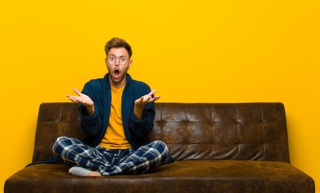 Młody człowiek w piżamie czuje się wyjątkowo zszokowany i zaskoczony, niespokojny i panikujący, zestresowany i przerażony. siedzieć na kanapie