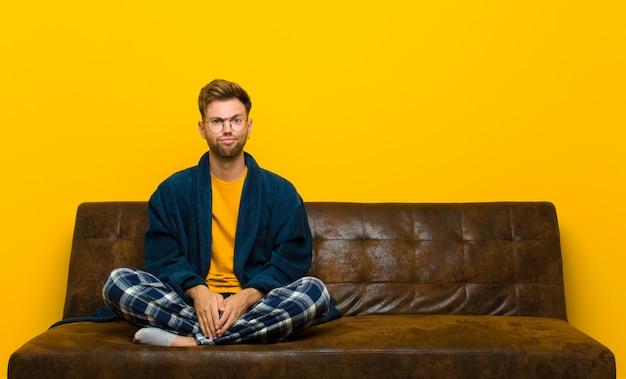 Młody człowiek w piżamie czuje się zdezorientowany i niepewny, zastanawia się lub próbuje wybrać lub podjąć decyzję. siedzieć na kanapie