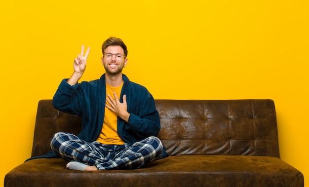 Młody człowiek w piżamie, patrząc szczęśliwy, pewny siebie i godny zaufania, uśmiechnięty i pokazując znak zwycięstwa, z pozytywnym nastawieniem. siedzieć na kanapie