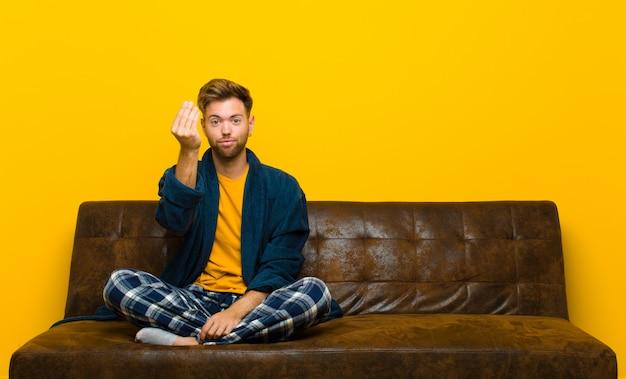Młody człowiek w piżamie robi pieniądze gestowi