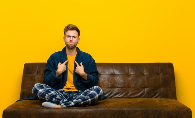 Młody człowiek w piżamie skierowanej ku sobie z zmieszanym i pytającym spojrzeniem zszokowany i zaskoczony wyborem. siedzieć na kanapie