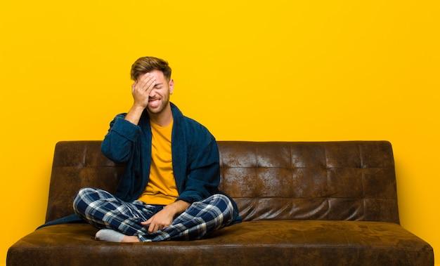 """Młody człowiek w piżamie, śmiejąc się i klepiąc się po czole, jak mówiąc: """"och!""""! zapomniałem lub to był głupi błąd"""