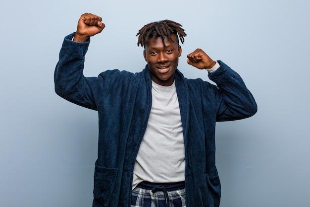Młody człowiek w piżamie z okazji specjalnego dnia, skacze i energicznie podnosi ręce