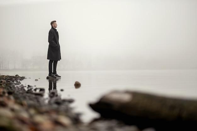 Młody człowiek w płaszcz jesiennej mgle morskiej