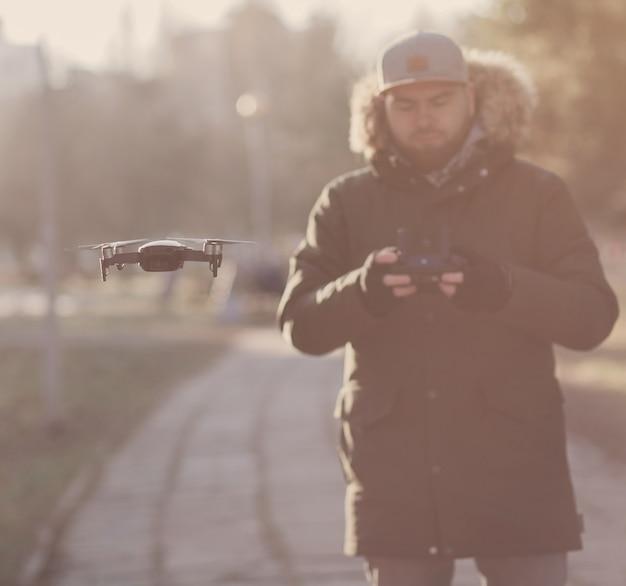 Młody człowiek w płaszczu nawigujący latającym dronem w parku.
