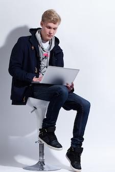 Młody człowiek w płaszczu z notebooka