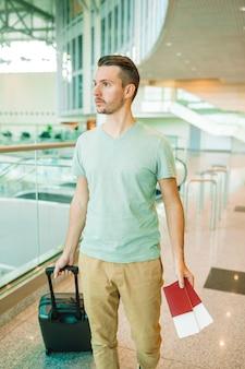 Młody człowiek w poczekalni na lotnisko samolotem.
