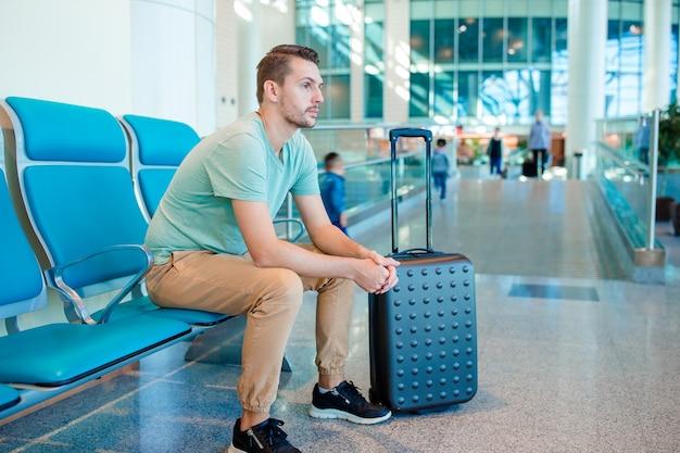Młody człowiek w poczekalni na lotnisku czeka na samolot lotu.