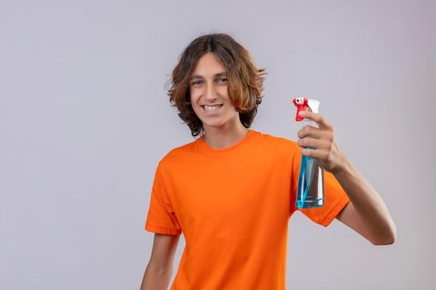 Młody człowiek w pomarańczowej koszulce gospodarstwa spray do czyszczenia patrząc na kamery uśmiechnięty wesoło szczęśliwy i pozytywny pozycja na białym tle