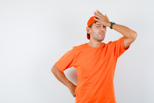 Młody człowiek w pomarańczowej koszulce i czapce, trzymając rękę na czole i patrząc przepraszam