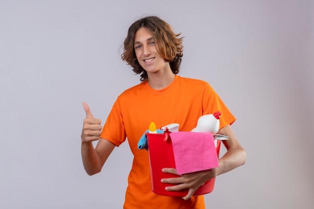 Młody człowiek w pomarańczowej koszulce trzyma wiadro z narzędzi do czyszczenia patrząc na kamery uśmiechnięty radośnie pokazując kciuki stojących na białym tle