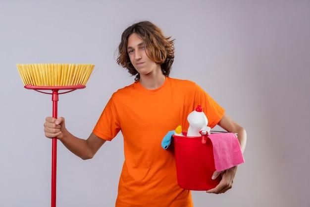 Młody człowiek w pomarańczowej koszulce trzyma wiadro z narzędziami do czyszczenia i mopem patrząc na kamery z pewnym uśmiechem na twarzy stojącej na białym tle