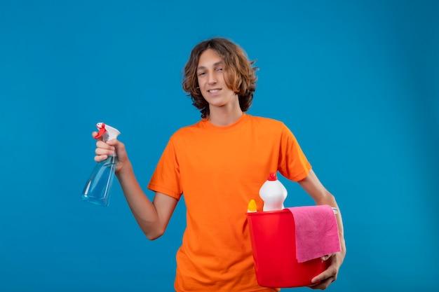 Młody człowiek w pomarańczowej koszulce trzyma wiadro z narzędziami do czyszczenia i sprayem do czyszczenia patrząc na kamery z pewnym uśmiechem na twarzy stojącej na niebieskim tle