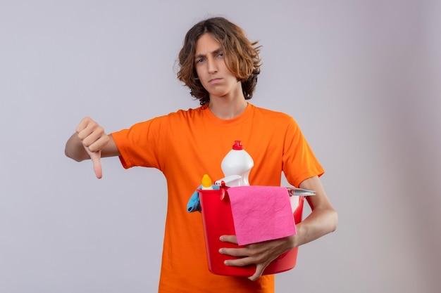 Młody człowiek w pomarańczowej koszulce, trzymając wiadro z narzędziami do czyszczenia, patrząc na kamery niezadowolony, pokazując kciuk w dół stojący na białym tle