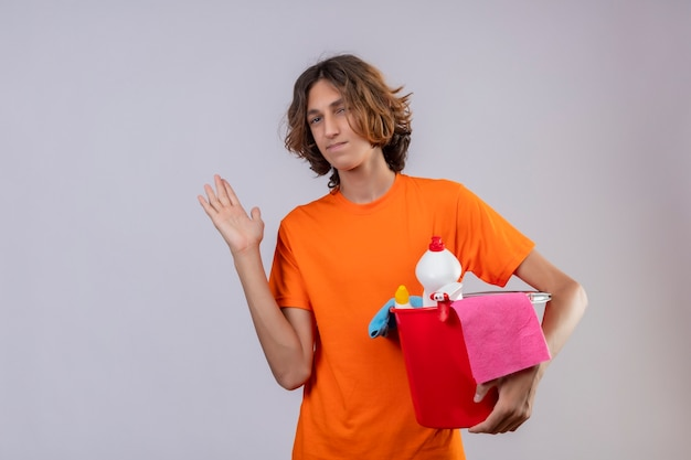 Młody człowiek w pomarańczowej koszulce, trzymając wiadro z narzędziami do czyszczenia, patrząc pewnie uśmiechnięty stojący z podniesioną ręką na białym tle
