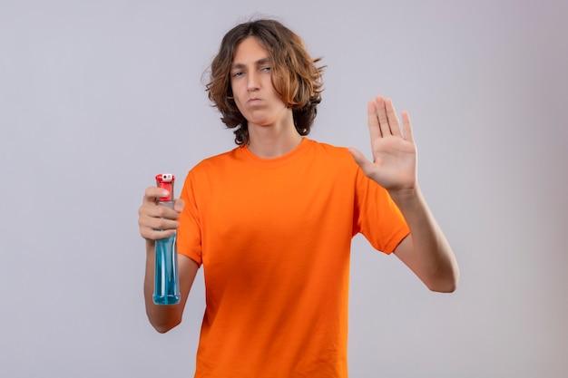 Młody człowiek w pomarańczowej koszulce trzymający spray do czyszczenia robiący znak stopu z gestem obrony dłoni patrząc na kamerę z marszczoną twarzą stojącą na białym tle