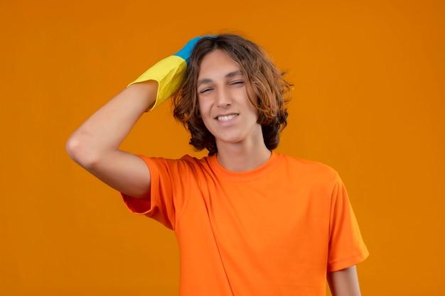 Młody człowiek w pomarańczowej koszulce w gumowych rękawiczkach, dotykając głowy za pomyłkę, patrząc zdezorientowanej koncepcji złej pamięci stojącej na żółtym tle
