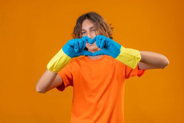 Młody człowiek w pomarańczowej koszulce w gumowych rękawiczkach robi romantyczny gest serca patrząc na kamery z uśmiechem na twarzy stojącej na żółtym tle