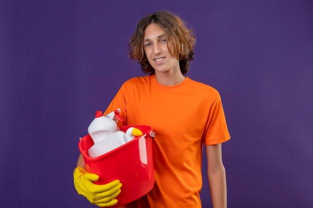 Młody człowiek w pomarańczowej koszulce w gumowych rękawiczkach trzyma wiadro z narzędziami do czyszczenia patrząc na kamery uśmiechnięty pozytywny i szczęśliwy stojący na fioletowym tle