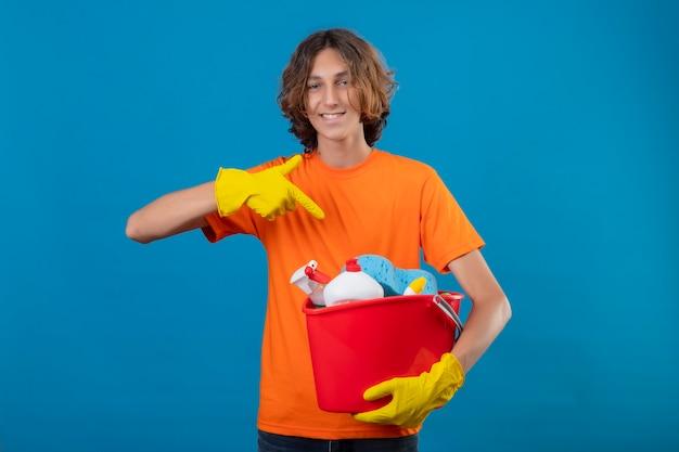 Młody człowiek w pomarańczowej koszulce w gumowych rękawiczkach trzyma wiadro z narzędziami do czyszczenia, wskazując palcem na niego, uśmiechnięty wesoło szczęśliwy i pozytywny stojąc na niebieskim tle