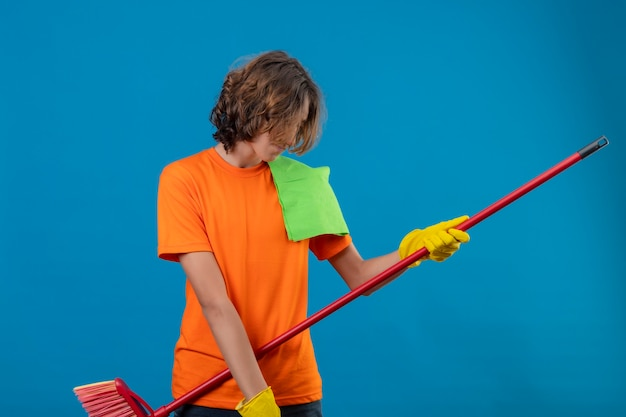 Młody człowiek w pomarańczowej koszulce w gumowych rękawiczkach trzymając mopa za pomocą gitary, zabawy patrząc radośnie stojąc na niebieskim tle