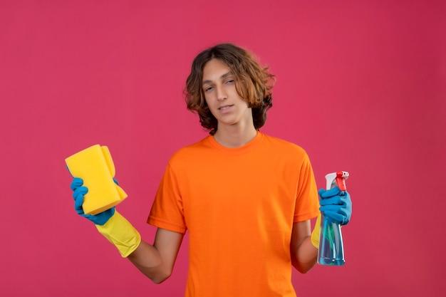 Młody człowiek w pomarańczowej koszulce w gumowych rękawiczkach, trzymając spray do czyszczenia i gąbkę, patrząc na kamerę z pewnym uśmiechem stojącym na różowym tle