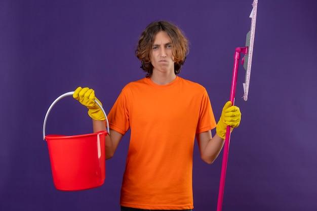 Młody człowiek w pomarańczowej koszulce w gumowych rękawiczkach, trzymając wiadro i mopa, patrząc na kamery z pewną poważną miną stojącą na fioletowym tle