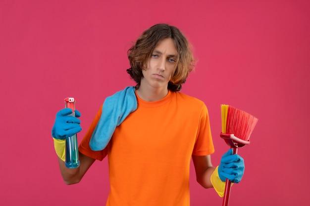 Młody człowiek w pomarańczowej koszulce w gumowych rękawiczkach trzymający mopa i spray do czyszczenia patrząc na kamerę ze smutnym wyrazem twarzy stojącej na różowym tle